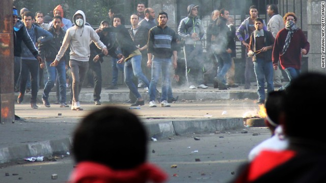 Muslim Brotherhood supporters (background) clash with supporters of the Egyptian government in Cairo on January 25, 2014.