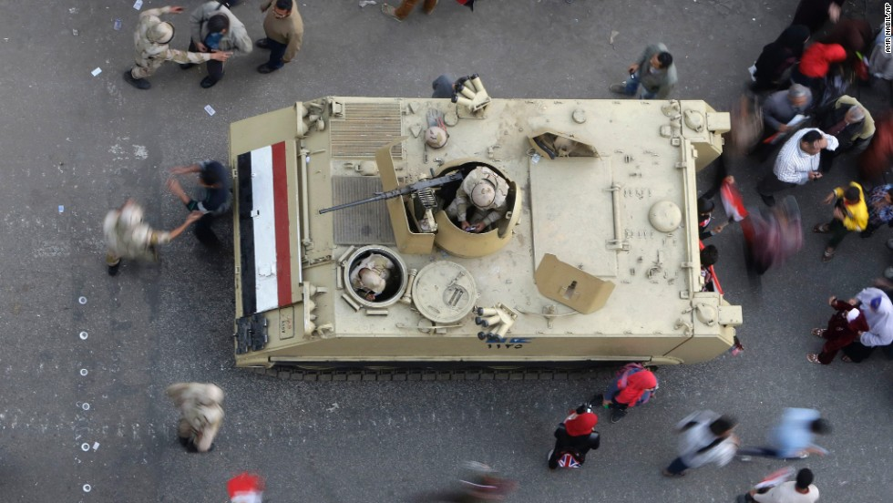 Egyptians walk around an armored personnel carrier parked at a pro-military rally in Tahrir Square.