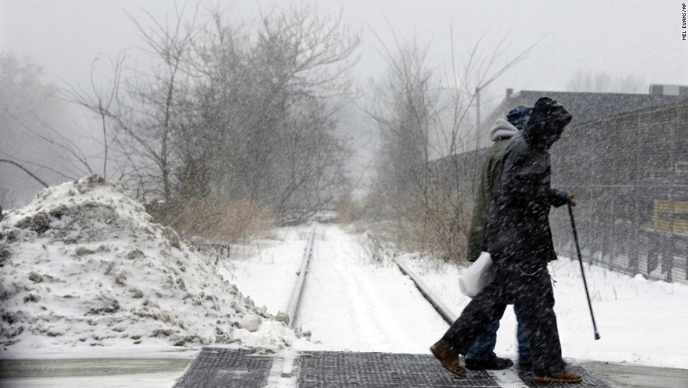 People walk in a snow squall January 25 in Trenton, New Jersey.