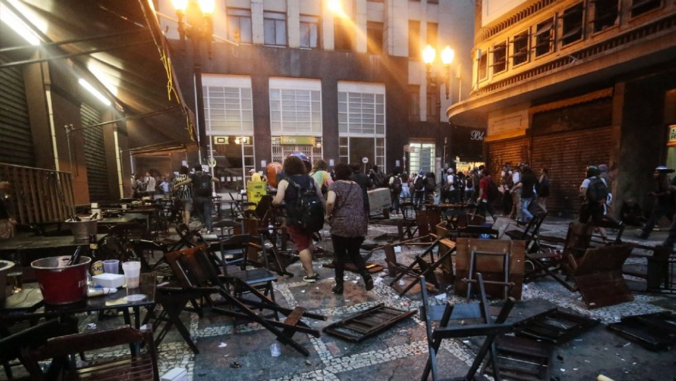 People walk among tables and chairs trashed during the protest.