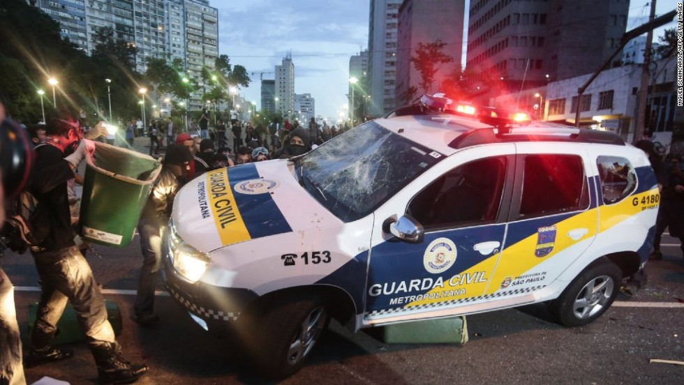 A civil guard car is attacked by demonstrators.