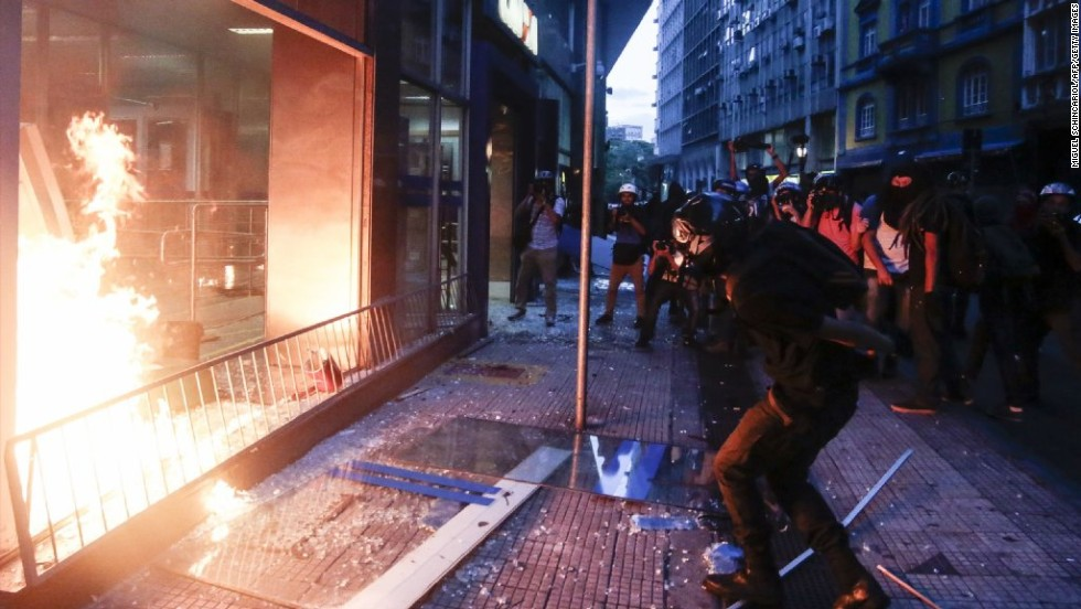 Demonstrators attack and set fire to a bank.