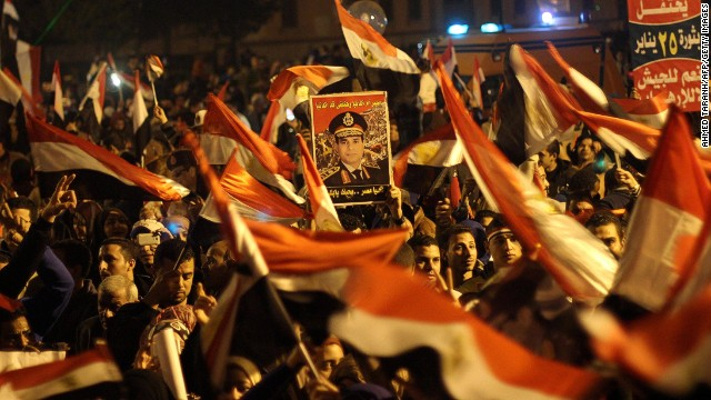 Egyptians wave the national flag and hold up pictures of Defence Minister army chief Abdel Fattah al-Sisi in General Abdel Monim Riyad Square in Cairo on January 25, 2014.