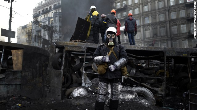 An anti-government protester, wearing a gas mask, stands at a road block in Kiev on January 26, 2014.