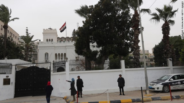 Women talk with policemen on January 25, 2014 in front of the Egyptian embassy, where Egyptian diplomats were seized earlier by kidnappers in Tripoli, Libya. At least 2 of the diplomats have been released.