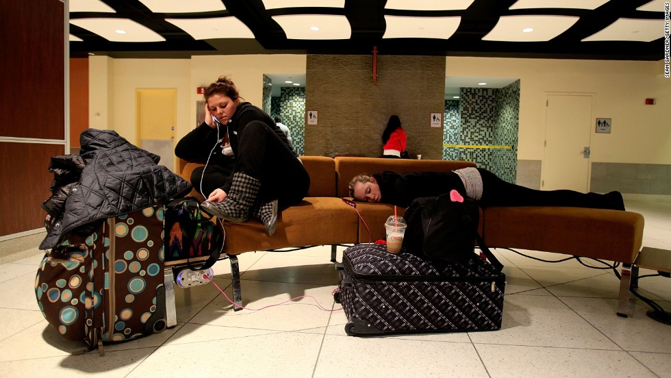 Two women are stranded at Louis Armstrong New Orleans International Airport on January 28 after flights were canceled due to the weather.