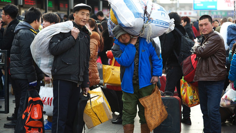 (L to R) Tang Zhiyuan, 61, Tang Zhongliang, 58, and Ding Wendong, 32, came to Beijing a year ago from Haicheng, Liaoning province. They work in logistics. Mr. Ding's bag is full of new clothes he bought for his family members. Mr. Tang, balancing a huge bag on his shoulder, bought some Beijing roast duck for the New Year's Eve dinner.