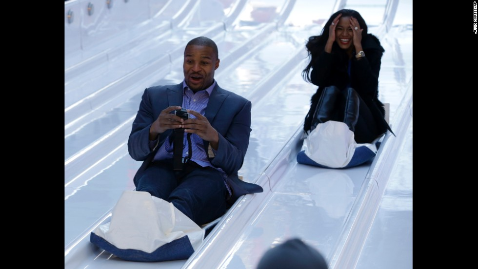 Atlanta Falcons defensive end Osi Umenyiora and his fiancee, Leila Lopes, slide down toboggans January 29 at Super Bowl Boulevard.