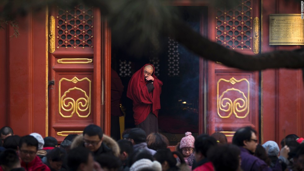 A monk stands at the entrance to the Yonghegong Lama Temple as people pray on the first day of the Lunar New Year.