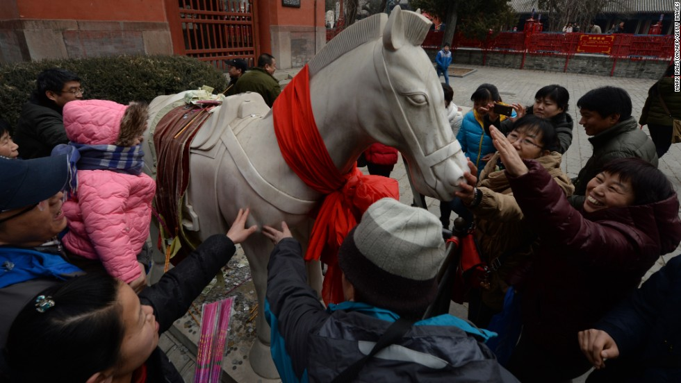 Visitors at the Dongyue Temple touch the White Jade Horse statue in the hope that it will bring them prosperity and good fortune in the Year of the Horse.