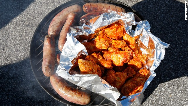 Sausages and chicken wings can be seen on a  barbecue grill as fans tailgate in the parking lots outside of Arrowhead Stadium prior to a week 1 NFL football game between the Atlanta Falcons against the Kansas City Chiefs in Kansas City, Missouri on September 9, 2012. The Falcons defeated the Chiefs 40-24. (AP Photo/Scott Boehm)