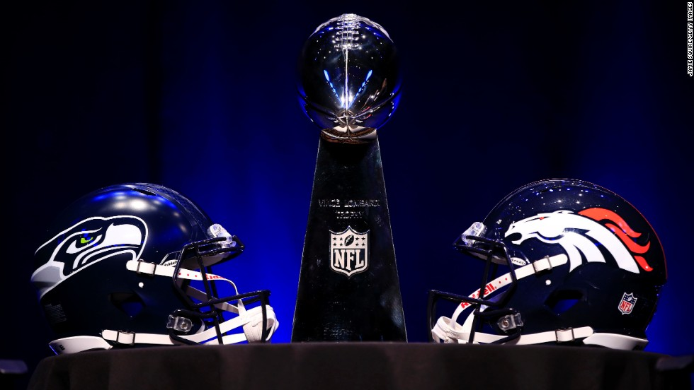 The Vince Lombardi Trophy is flanked by the helmets of the Seattle Seahawks and the Denver Broncos before the head coaches' news conference in New York on January 31.