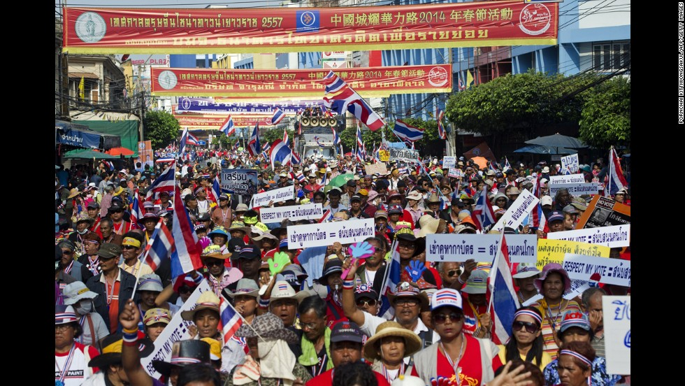 Anti-government protesters wave national flags during a parade in Bangkok.