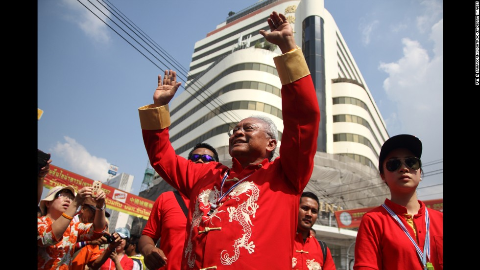 Anti-government protest leader Suthep Thaugsuban cheers during a march through Bangkok's Chinatown.