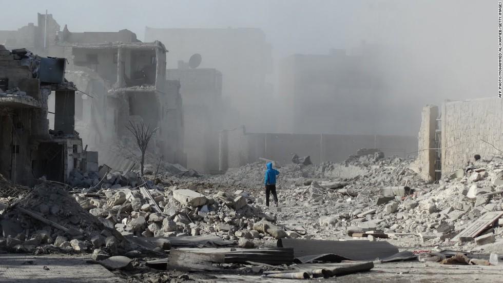 A man walks amid debris and dust on January 31.