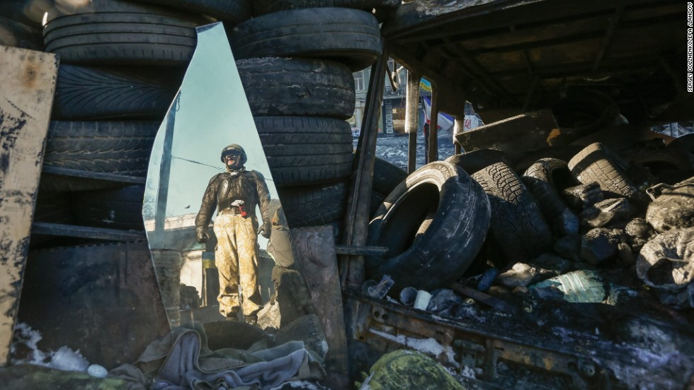 A protester is reflected in a broken mirror during protests in Kiev on Monday, February 3.