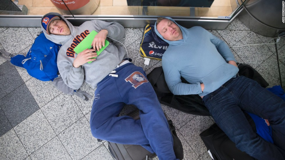 Drew Brown, left, and Matt Robbins sleep on the floor at LaGuardia Airport on February 3 after heavy snow in New York affected their flight. The winter storm stranded thousands of fans trying to head home after the Super Bowl.