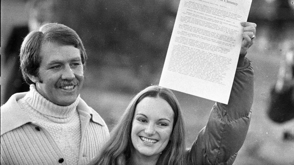 Hearst holds up the executive grant of clemency as she leaves prison on February 1, 1979. With her is her fiance and former bodyguard, Bernard Shaw.
