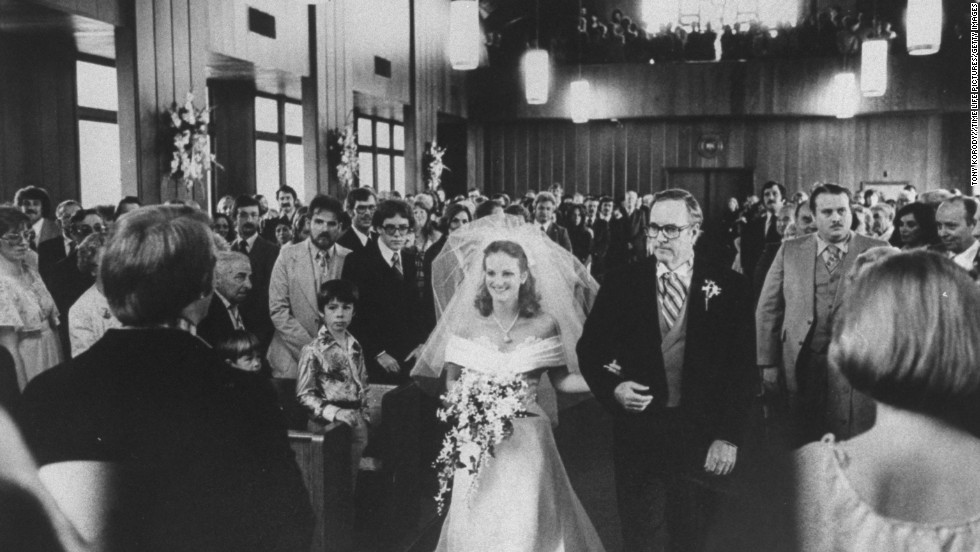 Hearst is walked down the aisle by her father, Randolph Hearst, at the Navy chapel at her wedding to Bernard Shaw in April 1979.