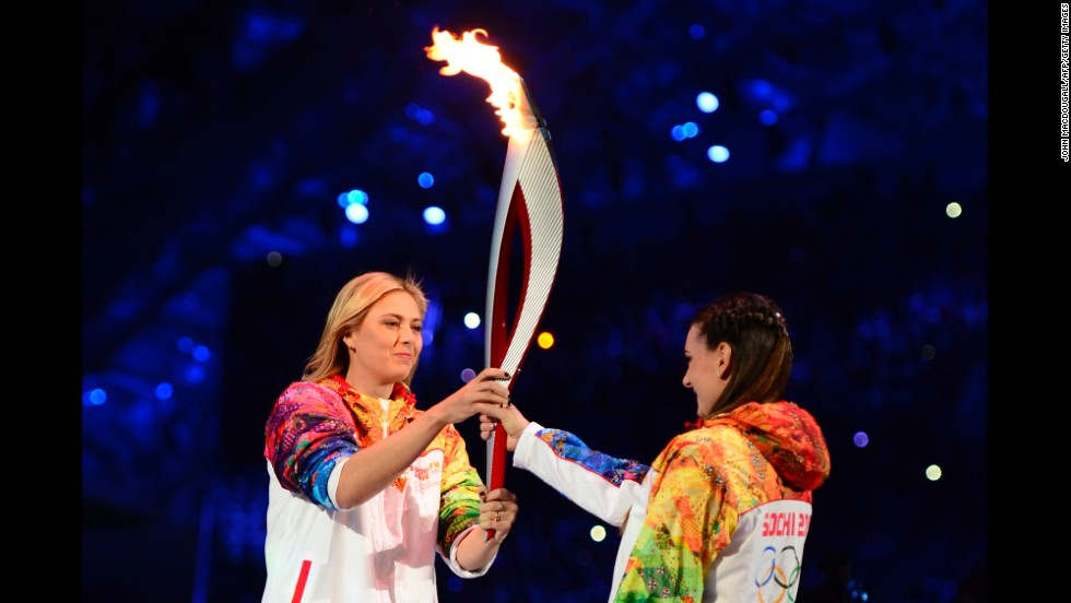 Russian tennis player and Olympic silver medalist Maria Sharapova, left, passes the Olympic torch to pole-vaulting legend Yelena Isinbayeva.