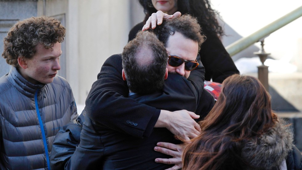 Writer David Bar Katz, wearing glasses, is embraced as he arrives at the church. Katz found Hoffman's body.