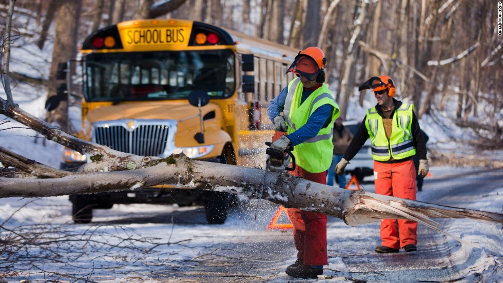 Workmen clear a downed tree blocking a school bus in the aftermath of a winter storm on Friday, February 7, in Downingtown, Pennsylvania. Utility companies scrambled to restore power to parts of the Northeast early Friday as hundreds of thousands shivered in the dark after a powerful snowstorm.