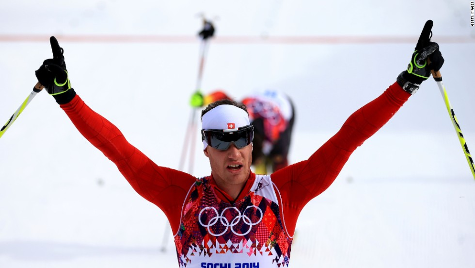 Dario Cologna of Switzerland raises his arms in triumph after taking gold in the men's skiathlon 15 km classic/15 km freestyle event.