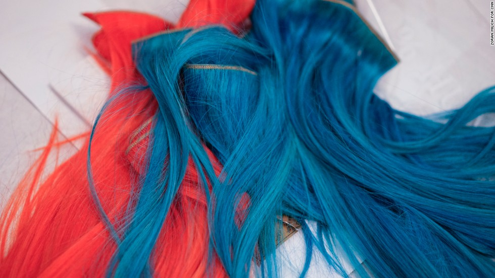 Blue and coral extensions are prepped for models' ponytails before the Herve Leger show.