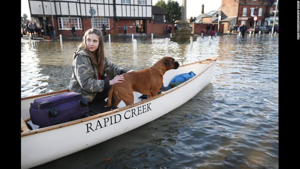 Beatrix Thurner and her family's dog, Ruby, leaves their flooded house in Datchet on February 10.