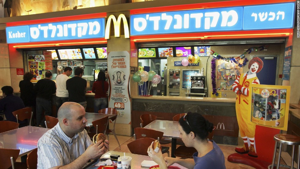 Israelis eat at a kosher McDonald's restaurant in Tel Aviv. After being pressured by Tel Aviv's Chief Rabbi, two of the city's McDonald's branches changed the color of their trademark signs to blue, indicating the availability of kosher food.