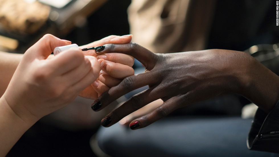 Essie nail polish is applied to a model before her turn on the runway for Mathieu Mirano.