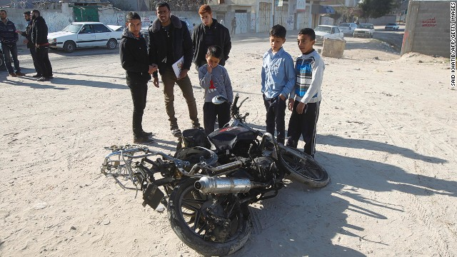 Palestinians look at the wreckage of a motorbike from an Israeli airstrike on February 9, 2014 in Gaza.