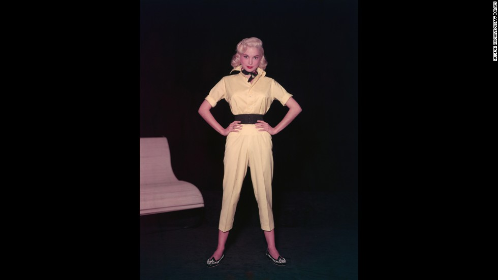 Actress Janet Leigh models a yellow short-legged jumpsuit with a wide belt, beaded shoes, and a neckerchief in the 1950s.
