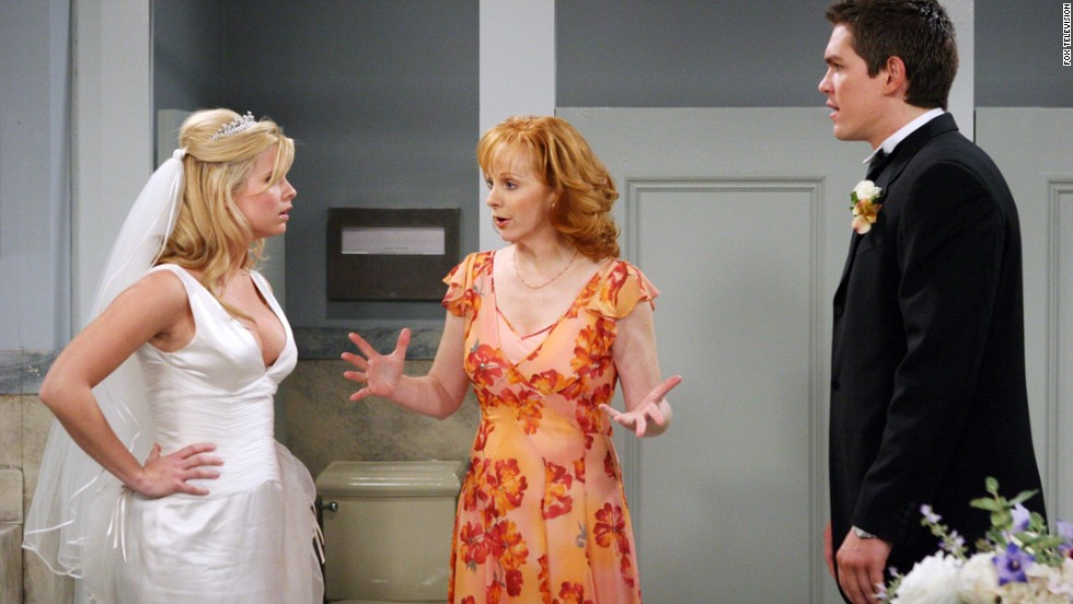 "Reba McEntire, center, as Reba Hart, who works as a secretary and later, a real estate agent, in ""Reba."""
