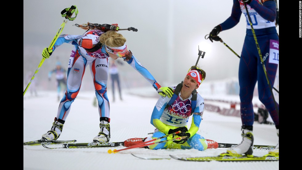 Slovenian biathlete Teja Gregorin, center, collapses at the finish line of the women's 10-kilometer pursuit on February 11.
