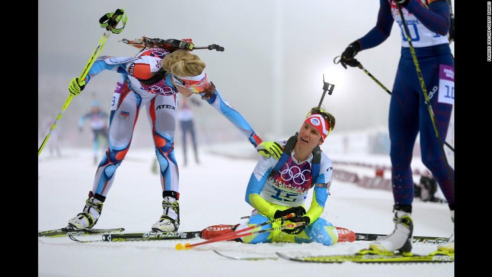 Slovenian biathlete Teja Gregorin, center, collapses at the finish line of the women's 10-kilometer pursuit on February 11.