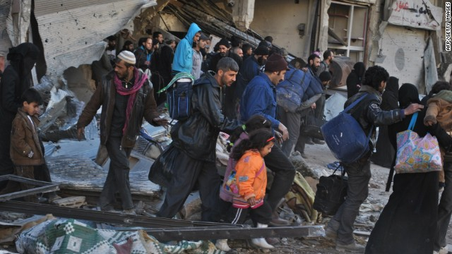 Syrian civilians walk as they are evacuated during a humanitarian operation in the besieged Syrian city of Homs on February 10, 2014.
