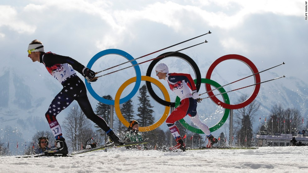 Andrew Newell of the United States leads Norway's Eirik Brandsdal as they ski past the Olympic rings during the men's cross-country sprint on Tuesday, February 11.