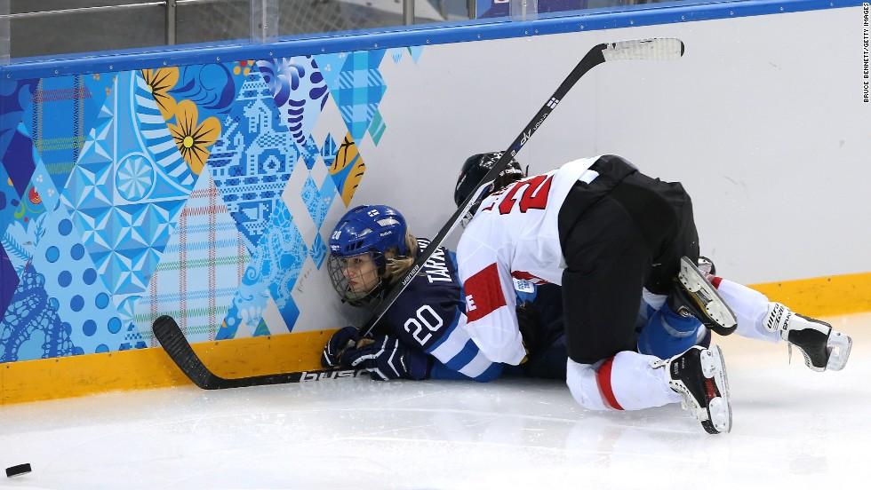 Laura Benz of Switzerland checks Saija Tarkki of Finland into the boards during a women's hockey game on February 12.