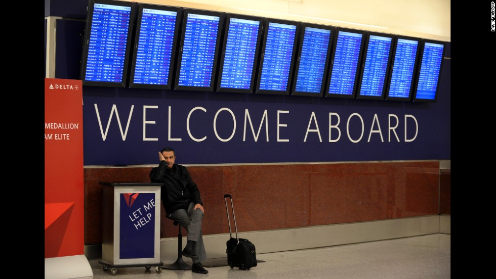 Hossam Shalaby waits for his rescheduled flight under a departure board at Hartsfield-Jackson Atlanta International Airport on Tuesday, February 11.