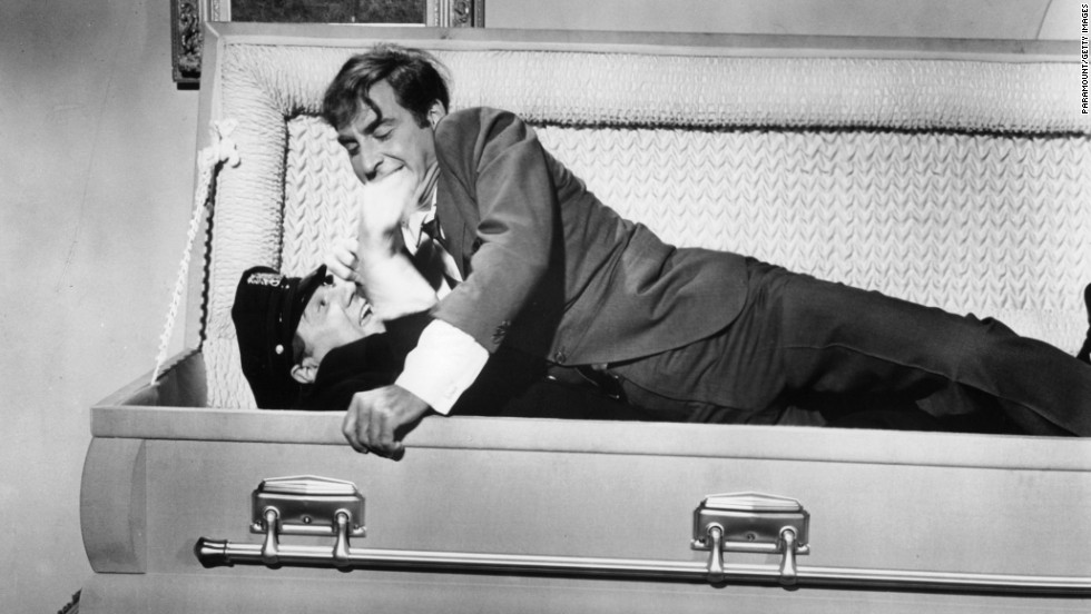 "In a scene from the 1966 film ""The Busy Body,"" Caesar lays on top of a cop in a coffin."
