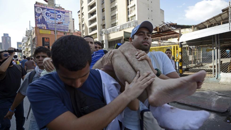 Jóvenes cargan a una persona herida durante las manifestaciones.