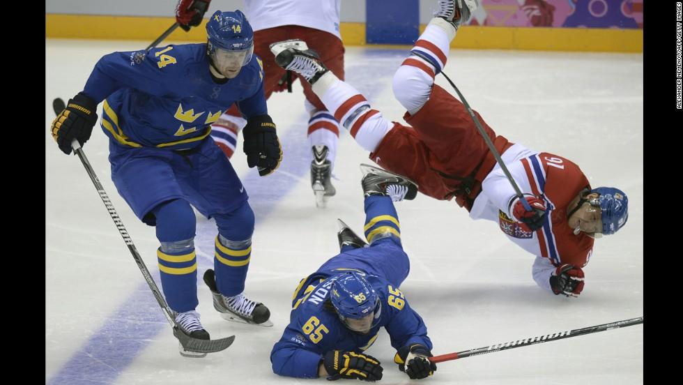 Czech hockey player Martin Erat, right, collides with Sweden's Erik Karlsson, bottom, and Patrik Berglund during their game on February 12.