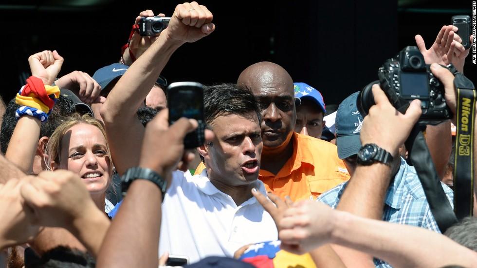 El líder opositor venezolano Leopoldo Lopez (C) saluda a sus seguiodres durante la marcha de protesta contra el gobierno de Nicolás Maduro.