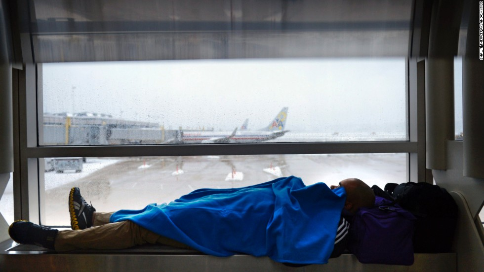 A traveler kills time as work crews continue to clear snow from the runways at Reagan National Airport in Arlington, Virginia, on February 13.