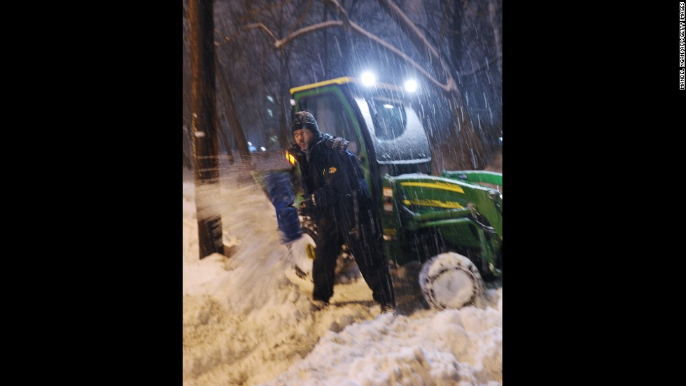 A man digs out a small snowplow that got stuck while clearing snow from a sidewalk in Chevy Chase, Maryland, on February 13.