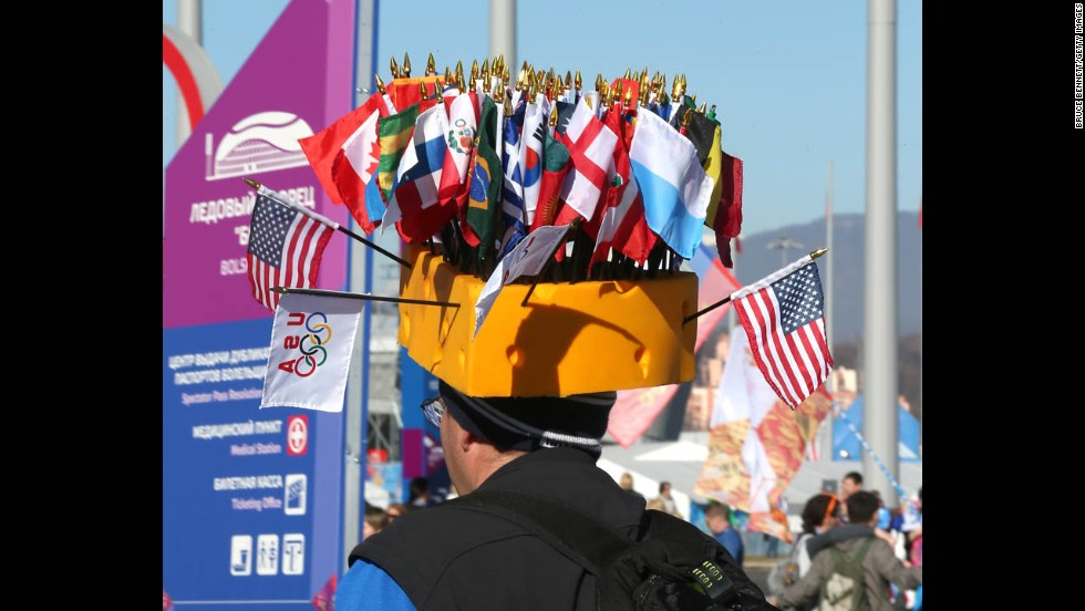 A man wears a hat adorned with the flags of different nations on February 13.