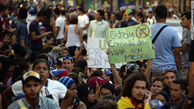 Students sit on the street as a protest against the death of a student who was killed on the eve during a demonstration against the government of Venezuelan President Nicolas Maduro, in Caracas, on February 13, 2014.