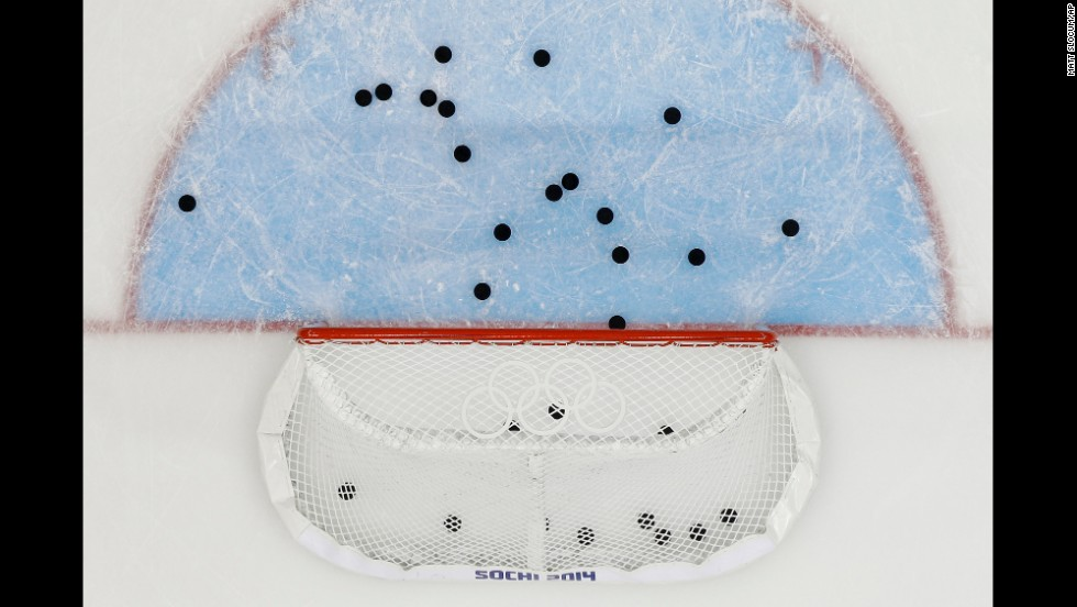 Pucks litter the ice around the net after the U.S. men's hockey team warmed up before its game against Slovakia on February 13.