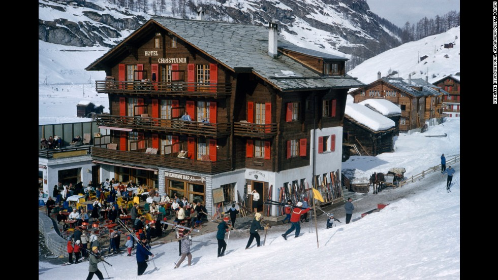 Skiing is hard work too. Skiers lug their gear while others kick back outdoors at a slopeside hotel in Zermatt, Switzerland in 1961.